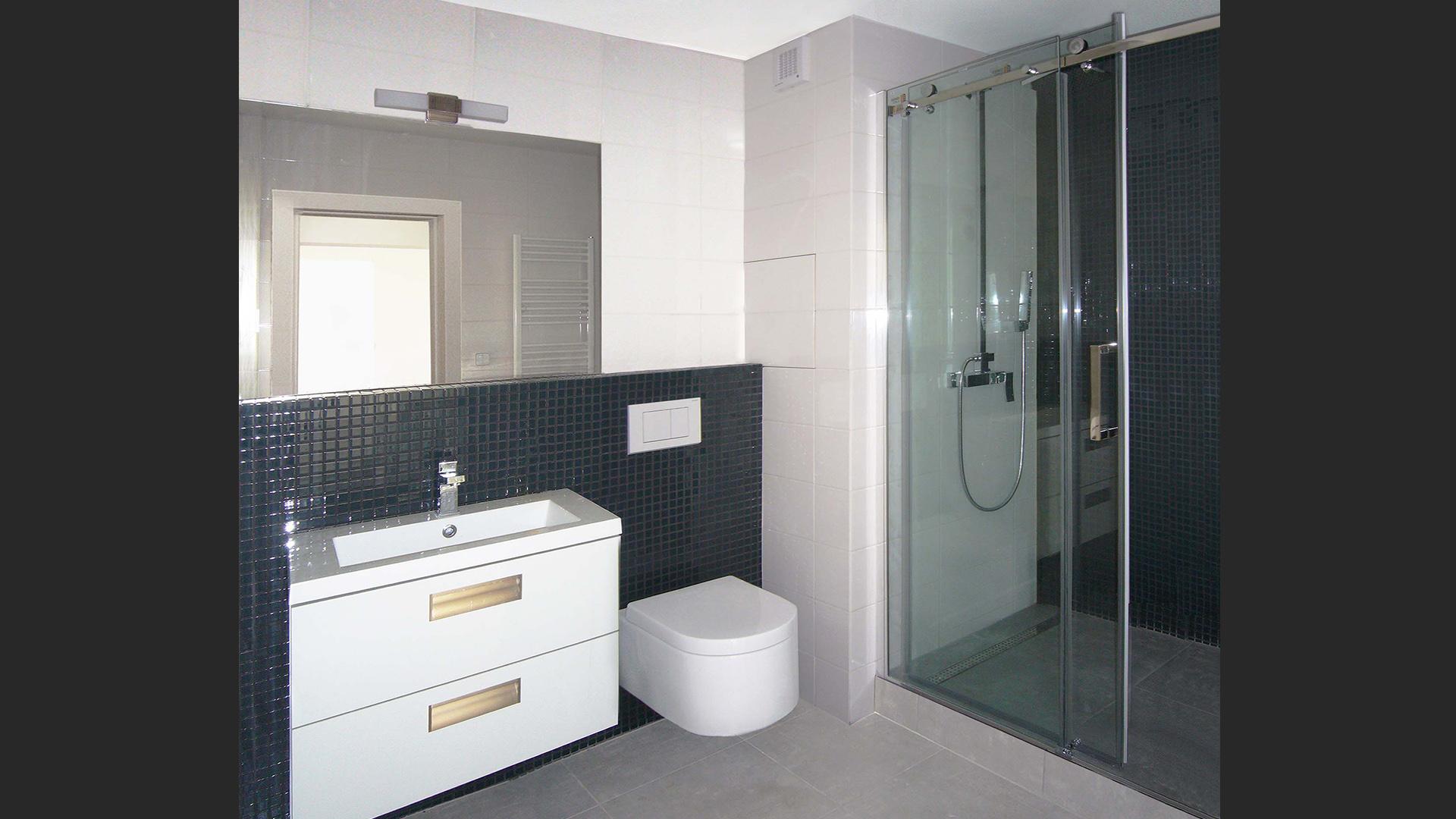 Celková rekonstrukce bytu s částečnou změnou dispozice v Praze na Žižkově na velikost 3 + kk. Pohled na koupelnu, která je obložená bílým lesklým obkladem v kombinaci s černou skleněnou