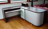 Pracovní stůl do obývacího pokoje na zakázku je vyroben z dýhy. Kombinace dřeva, kovových posuvných žaluzií, mléčného skla v kovovém rámečku na čelech zásuvek dávají nadčasovost a luxusnost tohoto solitéru. Doba realizace 2 týdny. Autor: Ing. arch. Marie Kulíková