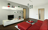 Celková rekonstrukce bytu se změnou dispozice v Praze v Modřanech. Nábytek je zhotovený na míru dle architektonického návrhu včetně Výběru svítidel a jiných doplňků. Červenobílá kombinace ladí s tmavěhnědou barvou lamina. Doba realizace 7 týdnů.